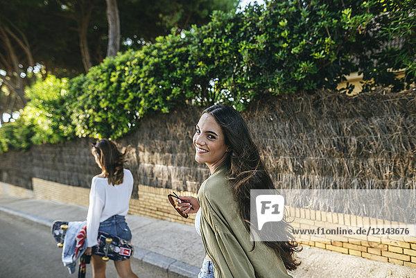 Porträt einer lachenden jungen Frau  die auf der Straße geht.