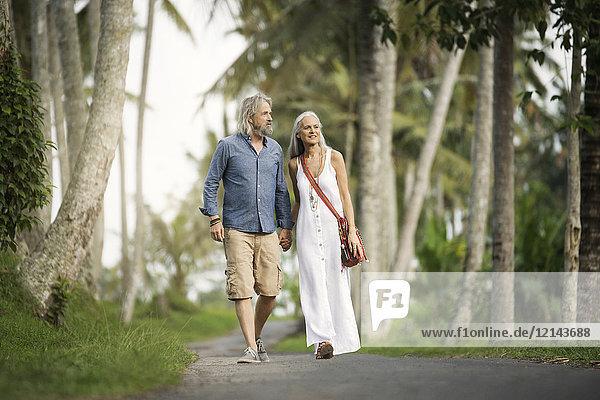 Hübsches Seniorenpaar beim Spaziergang durch tropische Landschaft mit Palmen