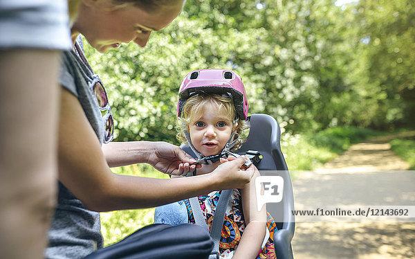 Kleines Mädchen sitzt auf einem Kindersitz für Fahrrad und ihre Mutter stellt ihren Helm ein