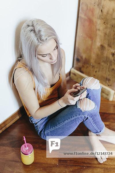 Junge Frau sitzt zu Hause auf dem Boden und benutzt ein Smartphone.
