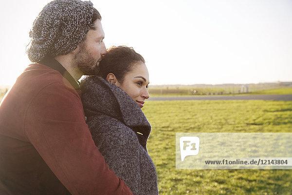 Zärtliches junges Paar  das sich auf einer Wiese umarmt.