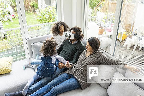 Glückliche Familie sitzend auf der Couch  Vater mit VR-Brille