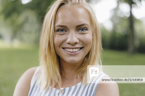 Porträt einer lächelnden jungen Frau im Park