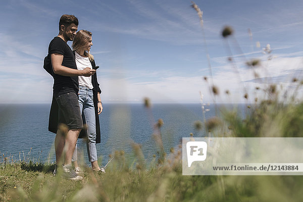 Junges Paar am Meer mit Blick auf das Smartphone