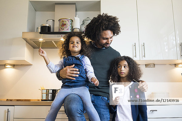 Vater steht mit seinen beiden Töchtern in der Küche.