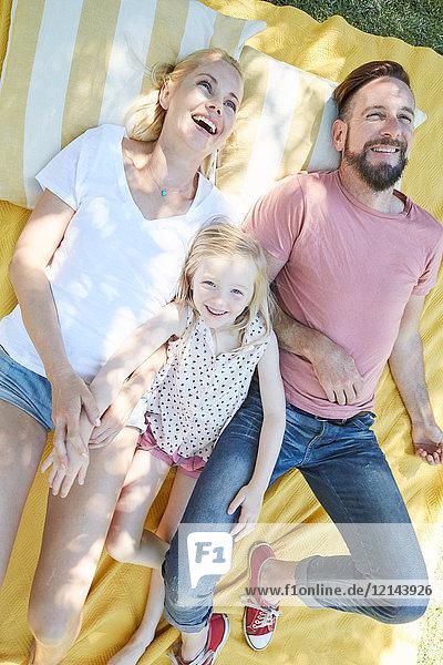 Glückliche Familie auf einer Decke liegend