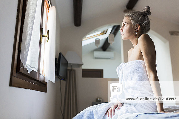 Young woman wrapped in a towel sitting on bed looking out of window