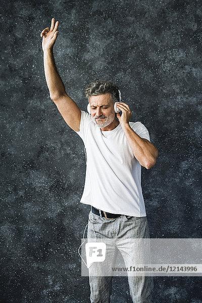 Erwachsener Mann mit Spaß an der Musik  Kopfhörer tragend