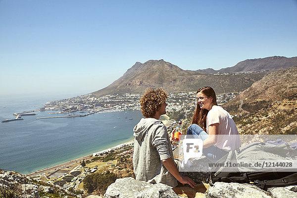 Südafrika  Kapstadt  lächelndes junges Paar an der Küste sitzend