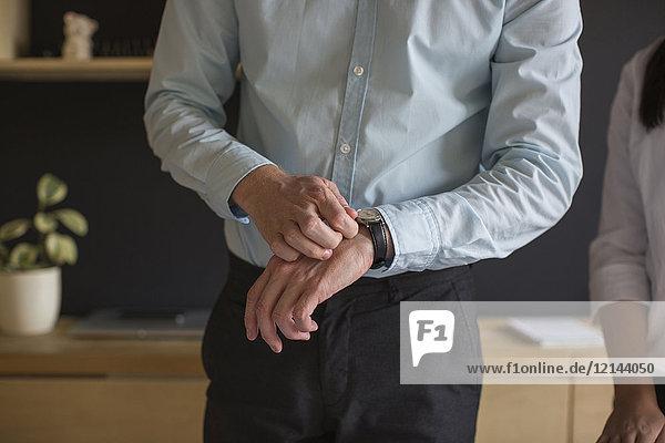 Geschäftsmann schaut auf seine Armbanduhr