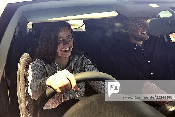 Glückliche junge Frau mit Freund beim Autofahren