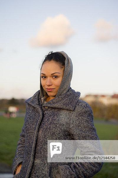 Porträt einer lächelnden jungen Frau in einem Mantel im Freien