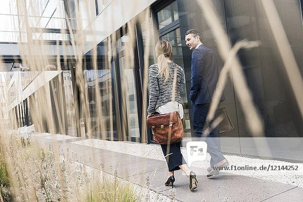 Geschäftsmann und Frau  die vor dem Bürogebäude spazieren gehen