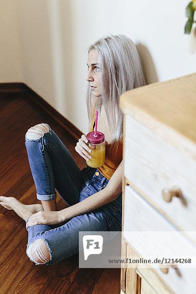 Seriöse junge Frau sitzt zu Hause auf dem Boden.