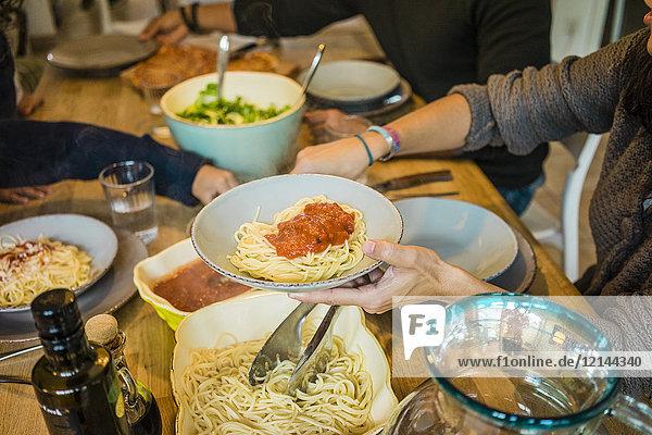 Familie am Tisch sitzend mit Spaghetti und Tomatensauce