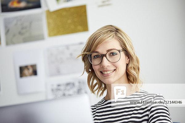 Portrait of smiling blond woman  glasses  pc