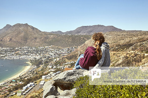 South Africa  Cape Town  young couple sitting at the coast looking at view