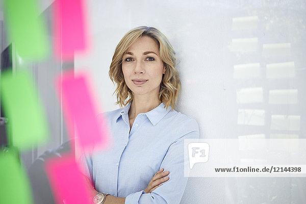 Porträt einer blonden Geschäftsfrau  Scheibe mit Notizblöcken