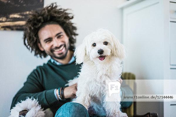 Süßer kleiner weißer Hund sitzt auf dem Schoß seines glücklichen Besitzers.