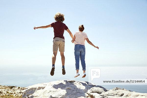 Südafrika  Kapstadt  junges Paar beim Sprung auf einen Berg an der Küste