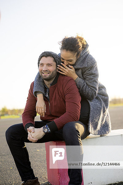 Glückliches junges Paar im Freien sitzend