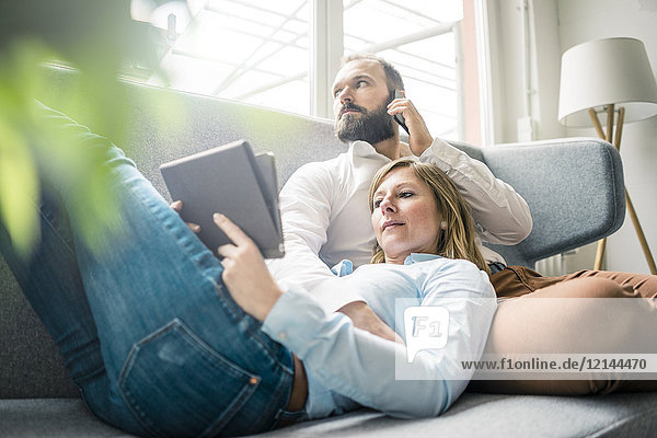 Couple using tablet and cell phone on couch