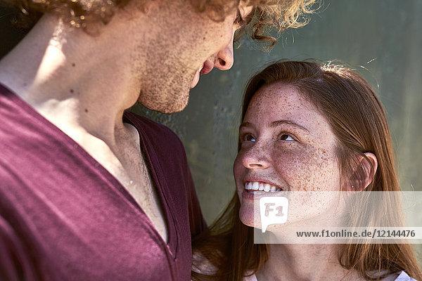 Lächelnde,  verliebte junge Frau,  die ihren Freund ansieht.