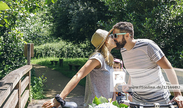 Couple with bicycles kissing with little daughter looking at them