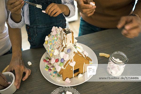 Familie klebt Lebkuchenhaus in der Küche für Weihnachten mit Süßigkeiten