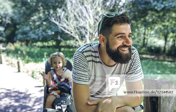 Father smiling with his daughter sitting in a child seat for bicycle