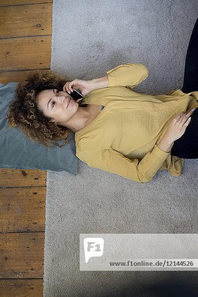 Junge Frau auf dem Handy zu Hause auf dem Boden liegend