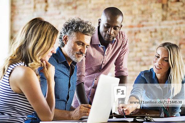 Geschäftsleute  die im Büro eines Start-up-Unternehmens arbeiten und eine Besprechung haben.