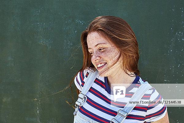 Lächelnde junge Frau mit Sommersprossen vor grüner Wand