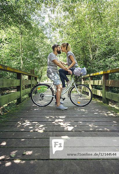 Paar mit Fahrrad  das sich auf einem Holzsteg auf dem Land küssen will.