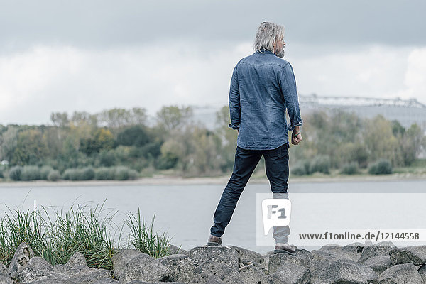 Älterer Mann auf Steinen stehend mit Blick auf den Rhein