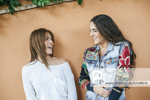 Two laughing friends in front of wall