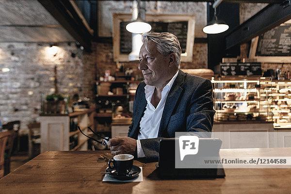 Senior Geschäftsmann sitzend im Cafe  mit digitalem Tablett  Tagträumen