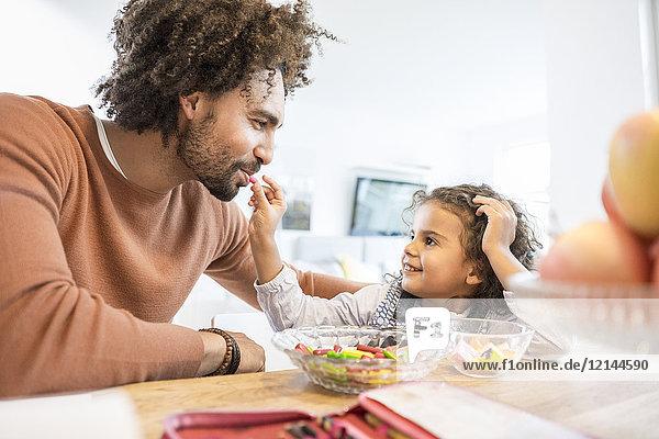 Lächelndes Mädchen füttert Vater zu Hause mit Süßigkeiten