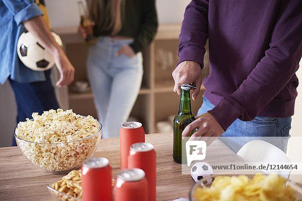 Fußballfan beim Öffnen einer Flasche Bier