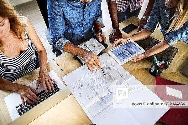 Kollegen diskutieren Blaupause am Schreibtisch im Büro