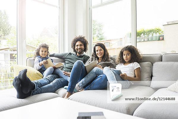 Glückliche Familie auf der Couch sitzend  Bücher lesend