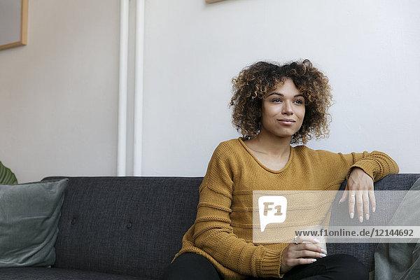 Lächelnde junge Frau  die zu Hause auf der Couch sitzt.