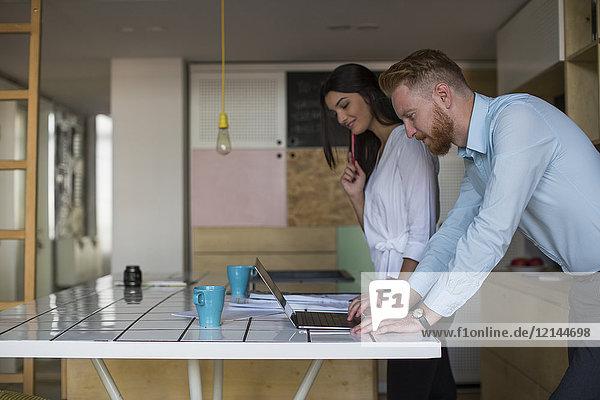 Lächelnder Mann mit Frau mit Laptop auf dem Tisch zu Hause