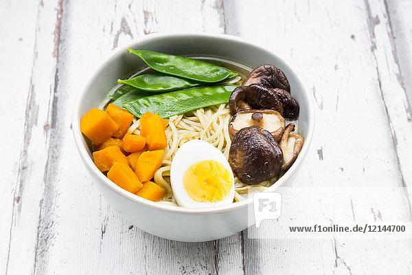 Ramen with noodles  egg  hokkaido pumpkin  mung sprout  shitake mushroom in bowl