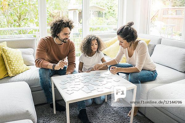 Familie auf der Couch sitzend  Gedächtnisspiel spielend