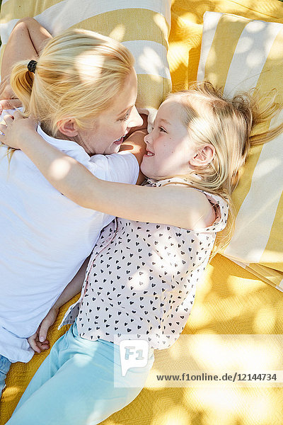 Glückliches Mädchen mit Mutter auf einer Decke liegend