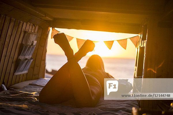 Spanien  Teneriffa  junge Frau im Van liegend  Abendlicht