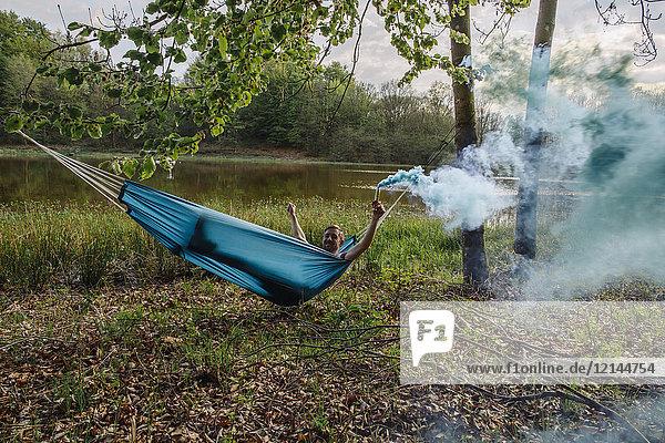 Junger Mann in Hängematte liegend mit blauer Rauchfackel