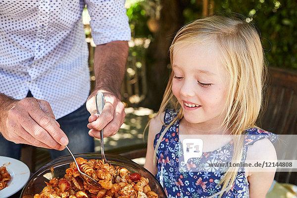 Vater bereitet Nudeln für die Tochter am Gartentisch auf.