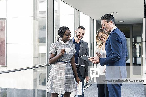 Lächelnde Geschäftsleute mit Tabletts im Bürogeschoss